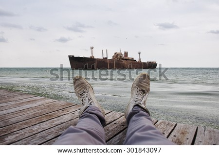 View of a wreck in the sea with his legs and feet in first - stock photo