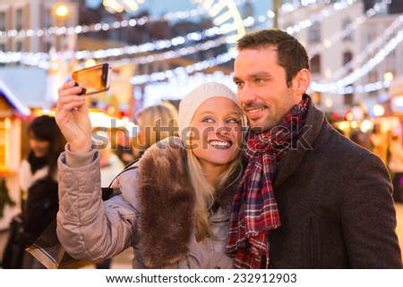 VIew of a Young attractive couple in a christmas market - stock photo
