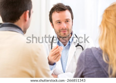 View of a Young attractive doctor advising a young couple of patients - stock photo