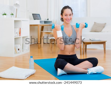 View of a Young attractive girl doing exercise at home with dumbell - stock photo