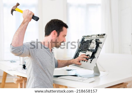 View of a Young attractive man angry against computer - stock photo
