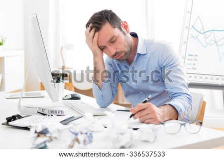 View of a Young attractive man too tired to work - stock photo
