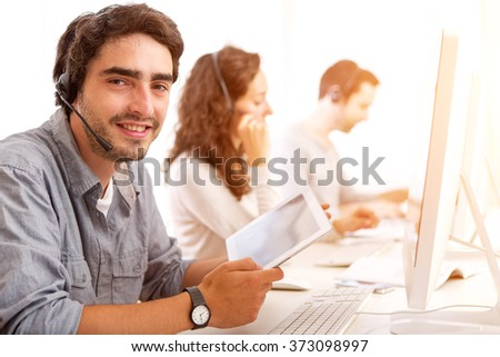 View of a Young attractive man working in a call center - stock photo