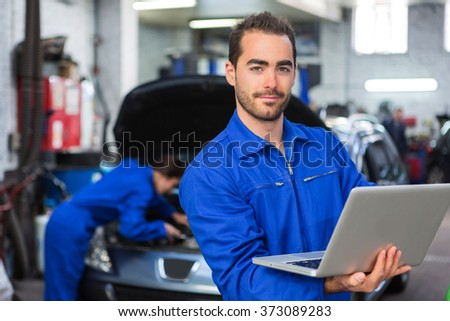 View of a Young attractive mechanic working at the garage - stock photo
