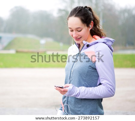 View of a Young attractive woman adjust her music player before running - stock photo