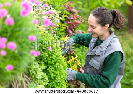 View of a Young attractive woman working in a public garden - stock photo