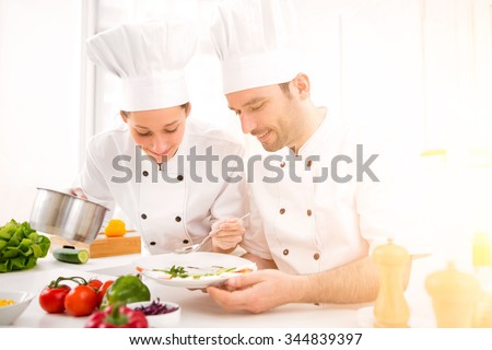 View of a Young attractives professionals chefs cooking together - stock photo