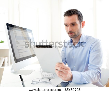View of a Young business man working at home on his tablet - stock photo