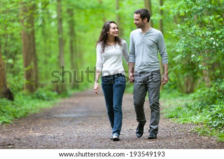 View of a Young couple having a walk in a forest - stock photo