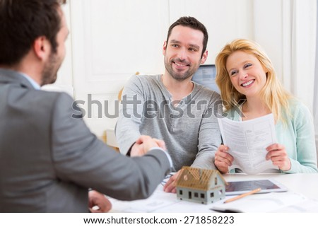 View of a Young happy couple handshaking real estate agent after signing contract - stock photo