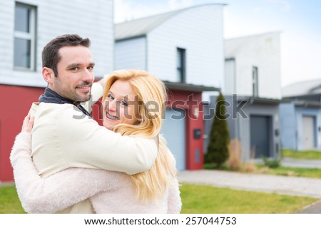 View of a Young happy couple in front of their new house - stock photo