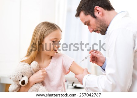 View of a Young little girl  being vaccinated at the doctor - stock photo