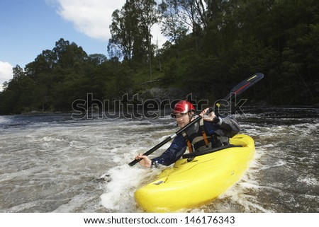 View of a young man kayaking in river - stock photo