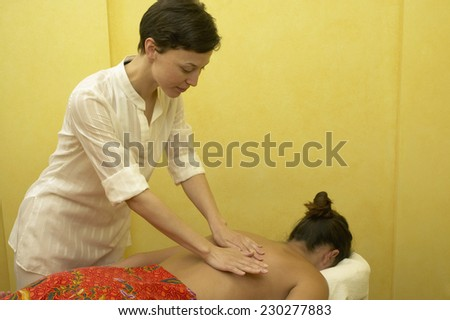 View of a young woman having a back massage - stock photo