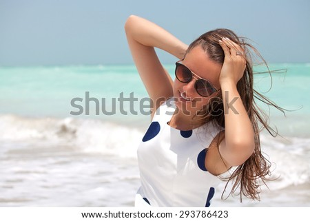 View of a young woman with the wind in her hair. Fashion shot on the beach. Beauty in the summer sun. - stock photo