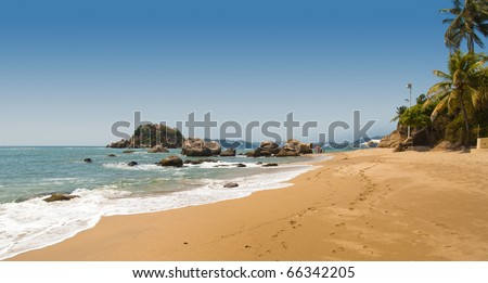 View of Acapulco Bay on a sunny day with beach cabanas - stock photo