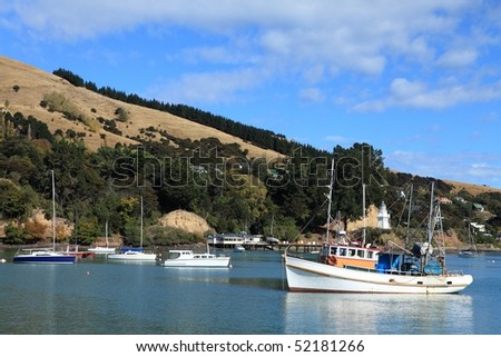 View of Akaroa Harbor, New Zealand, showing recreational boats, a fishing boat and the old restored Lighthouse in the background - stock photo