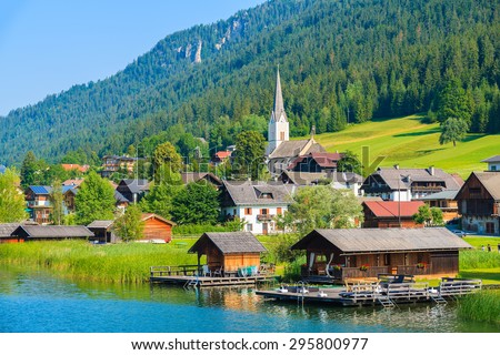 View of alpine village on shore of Weissensee lake in summer landscape Alps mountains, Austria - stock photo