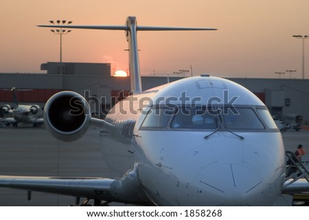 View of an airplane at the gate during sunset - stock photo