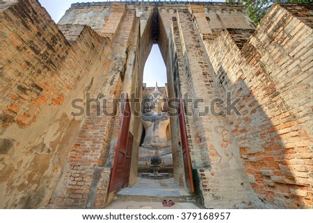 View of an ancient Buddha statue through the gate to Temple Wat Si Chum in Sukhothai Historical Park, Thailand ~ A giant sitting Buddha image with the posture of Subduing Mara inside a buddhist shrine - stock photo