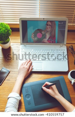 view of an artist drawing something on graphic tablet at the office - stock photo