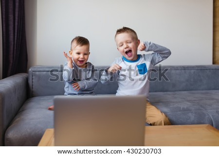 View of an excited boys  videocalling. Two cute siblings using laptop while sitting on sofa - stock photo