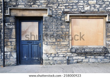 View of an Old Boarded-up Shop on a High Street in a Typical English Town - stock photo