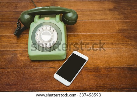 View of an old phone and a smartphone on wood desk - stock photo