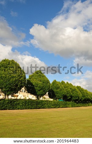 View of an Open Field, Tree Line and Blue Cloudy Sky in a Beautiful Green City Park - stock photo