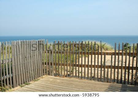 View of Atlantic Ocean through fence, Nauset Beach, Cape Cod, Massachusetts - stock photo