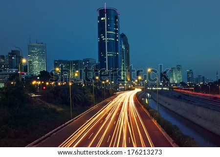 View of Ayalon highway, light traces and modern buildings in evening at downtown of Tel Aviv, Israel. - stock photo