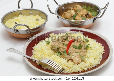View of balti chicken pasanda curry served on a bed of saffron rice, garnished with coriander leaves and a red chilli. - stock photo