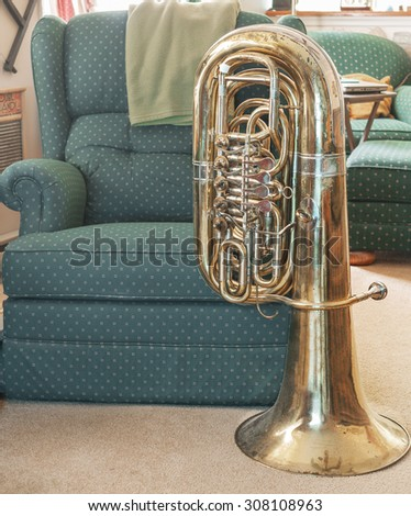 View of bass tuba in a comfortable, home setting, next to an easy chair/recliner. - stock photo