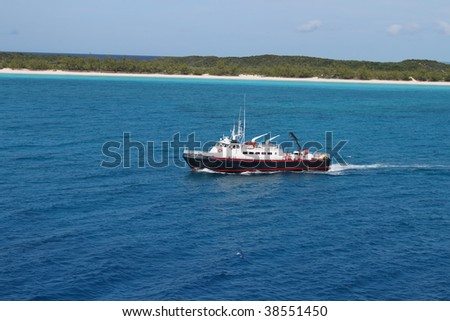 View of beach at Half Moon Cay in the Bahamas with boat approaching - stock photo