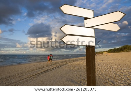 View of blank wooden multi-direction guidepost with people walking along the Baltic Sea coast just before sunset, Poland - stock photo