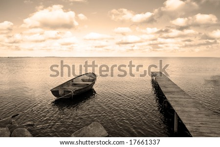 View of boat, bridge and calm sea. Ideal for background. Sepia tone. - stock photo