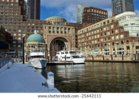 view of boston harbor and rowes wharf and skyscraper buildings in boston massachusetts with ships - stock photo