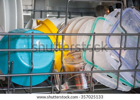 View of bottom rack of dishwasher loaded with plastic ware still wet - stock photo