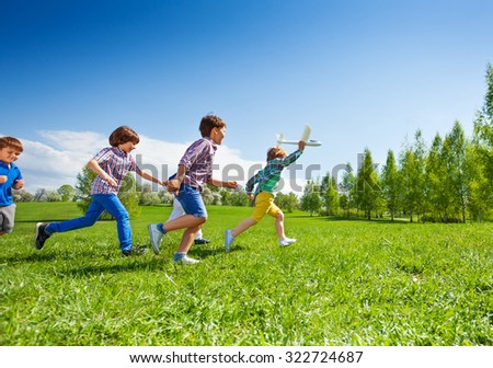 View of boy with airplane toy and following him children running happily together during beautiful sunny weather in park - stock photo