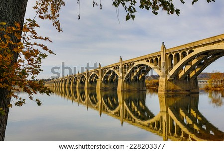 View of bridge across Susquehanna River in Pennsylvania with reflection in water shot horizontal. - stock photo