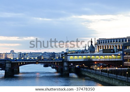 View of bridge and cityscape on Thames river in London at night - stock photo