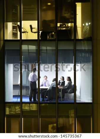 View of businessman giving presentation to colleagues in conference room through window at night - stock photo
