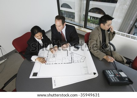 View of businesspeople checking blueprint with an architect speaking on phone. - stock photo