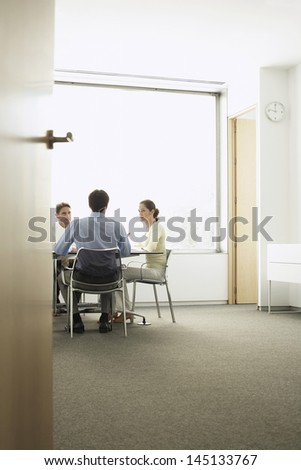 View of businesspeople discussing during meeting in boardroom though doorway - stock photo