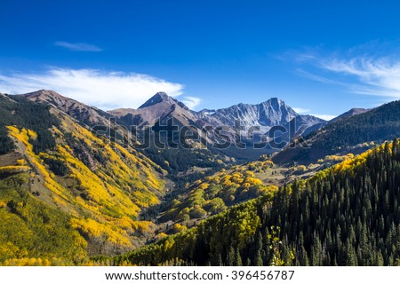View of Capitol Peak near Aspen Colorado surrounded by valley filled with changing yellow Aspen trees on sunny autumn afternoon - stock photo