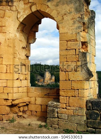 View of Chateau Laussel through an arched window of Chateau de Commarque in the Dordogne, France - stock photo