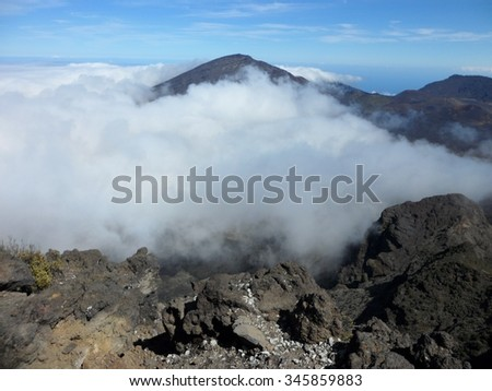 View of clouds in volcanic crater from Leleiwi Overlook at 8,840 feet elevation on Haleakala, Maui, Hawaii, USA - stock photo