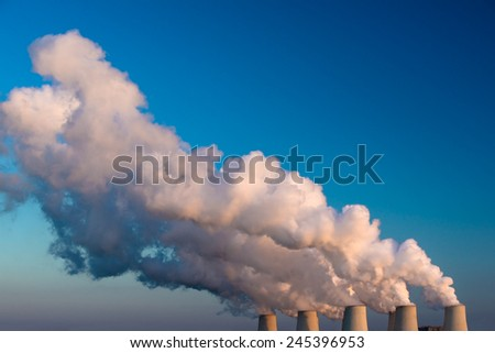 View of coal power plant on sunset with several chimneys and huge fumes  - stock photo