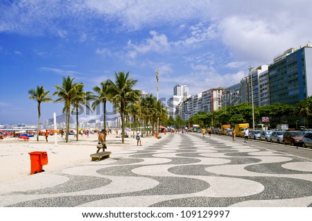 View of Copacabana beach with palms and mosaic of sidewalk - stock photo