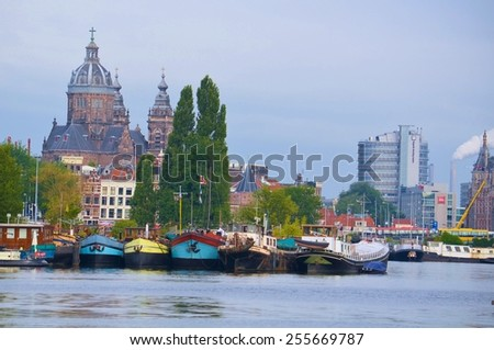 view of de oude kerk in amsterdam with ships anchoring nearby. - stock photo